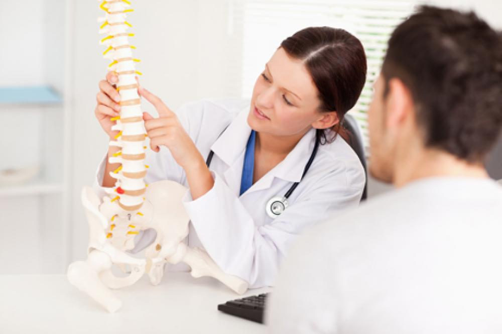 Chiropractor going over possible bulging discs that occur in the spine
